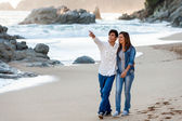 Young couple wandering along seashore.
