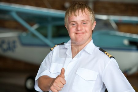 Photo for Portrait of young handicapped pilot showing thumbs up in hangar. - Royalty Free Image