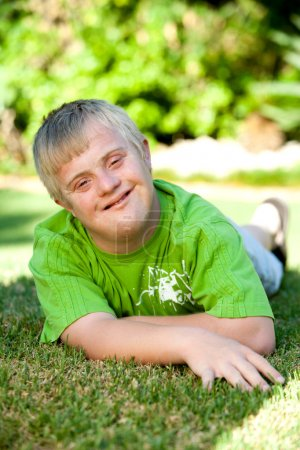 Portrait of handicapped boy on green grass.