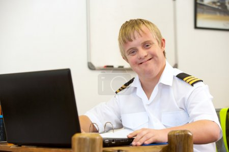 Portrait of young pilot with down syndrome at desk.