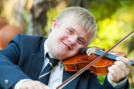 Photo for Portrait of young handicapped violinist practicing outdoors. - Royalty Free Image