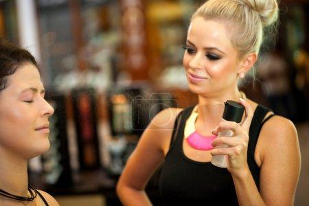 Photo pour Gros plan de maquillage mignon artiste en utilisant spray fixateur sur le visage des filles . - image libre de droit