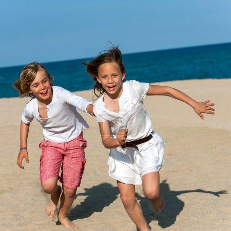 Boy chasing girl on beach.