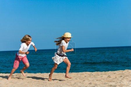 Boy chasing girlfriend on beach.