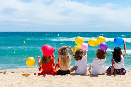 Photo pour Jeunes enfants tenant des ballons de couleur assis sur la plage . - image libre de droit
