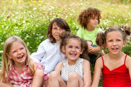 Photo pour Groupe d'amis assis ensemble dans un lit de fleurs . - image libre de droit
