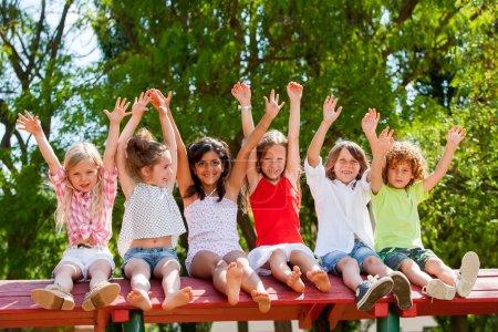 Happy kids raising hands outdoors.