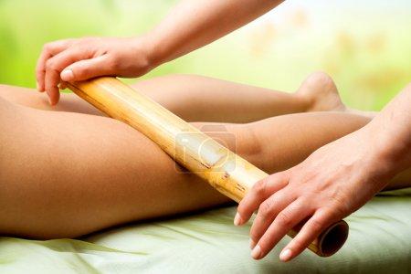 Photo pour Gros plan des mains de thérapeute massage jambes femmes avec bâton de bambou. - image libre de droit