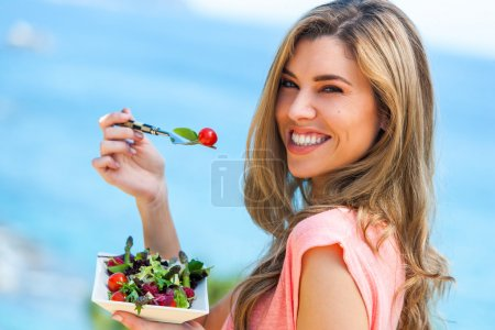 Photo for Portrait of beautiful young woman holding green salad outdoors at seaside. - Royalty Free Image