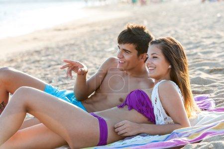 Teen couple enjoying afternoon on beach.