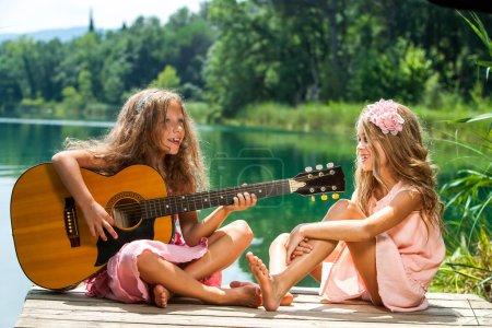 Girlfriends singing together at lake.