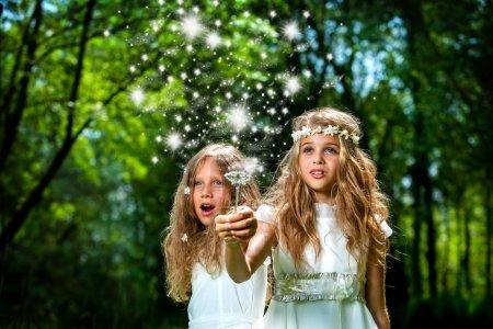 Girls casting magic spells in woods.
