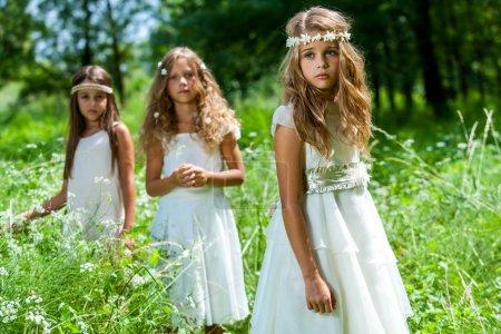 Three girls wearing white dresses in woods.
