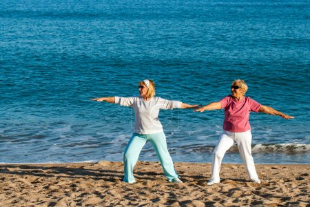 Senior ladies doing yoga on beach.