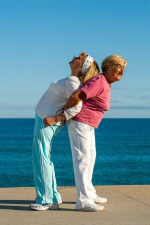 Photo pour Portrait de deux dames seniors entraider avec des étirements exercice en plein air. - image libre de droit