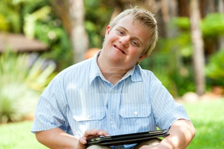 Photo for Close up portrait of handicapped boy playing on digital tablet outdoors. - Royalty Free Image