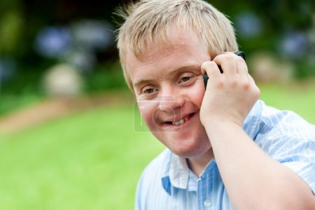Photo for Close up portrait of handicapped boy talking on smart phone outdoors. - Royalty Free Image