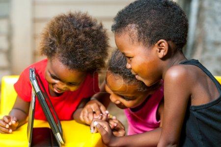 Photo pour Gros plan portrait de trois jeunes filles africaines jouant ensemble sur tablette numérique . - image libre de droit