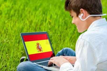 Photo for Close up of teen student taking spanish audio lessons on laptop outdoors. - Royalty Free Image