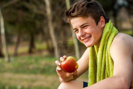 Teen eating apple after ecercise.