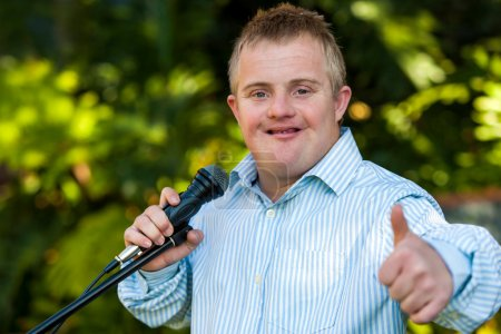 Handicapped boy with microphone doing thumbs up.