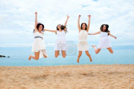 Photo pour Groupe de jeunes adolescentes sautant ensemble sur la plage . - image libre de droit