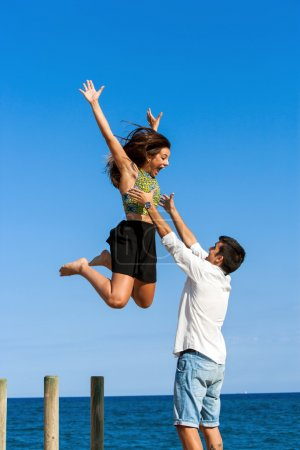 Young man catching girlfriend in air