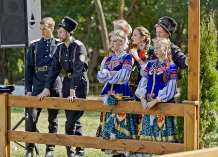 Photo pour Hommes et femmes membres de l'ensemble folklorique en costumes de cosaques des troupes cosaques Terek pendant les vacances en ville - image libre de droit