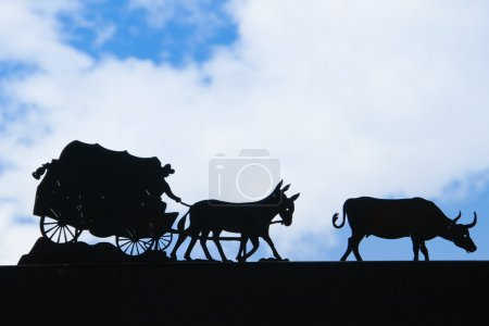Covered wagon silhouetted with blue sky