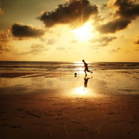 Photo for Silhouette of man playing football on the beach - Royalty Free Image