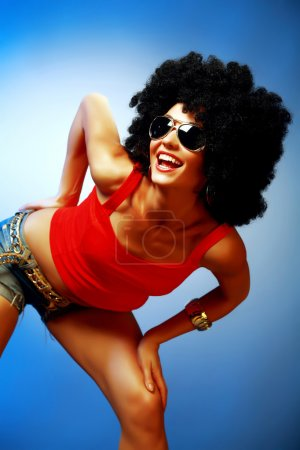 Smiling tanned woman with afro hair posing against blue background