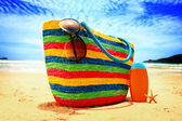 Colorful straw bag, sunglasses, bottle of sun lotion and starfish on paradise tropical beach