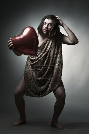 Wild man in leopard skin hold big red heart.