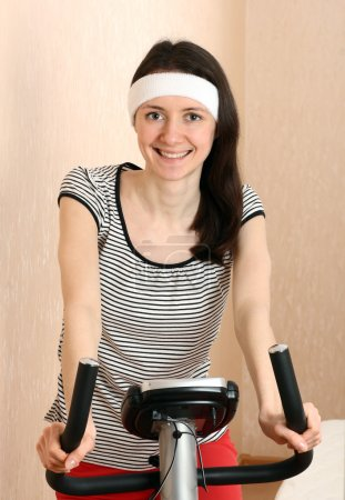 Attractive young brunette on a training bicycle