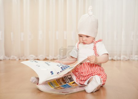 Little baby girl examining a big magazine at home