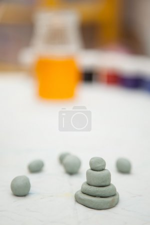 Small clay toys and paint on a table