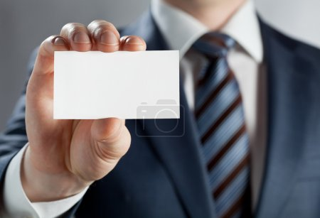 Photo for Man's hand showing business card - closeup shot on grey background - Royalty Free Image