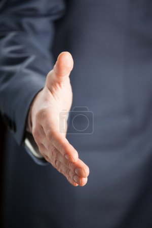 Businessman offering handshake to you