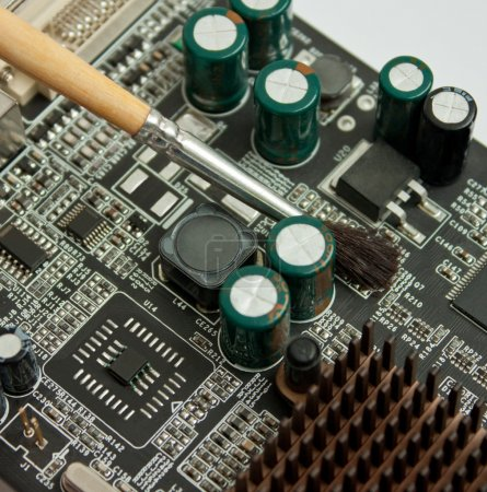 Photo for Cleaning computer electronic board. closeup of video card and brush - Royalty Free Image