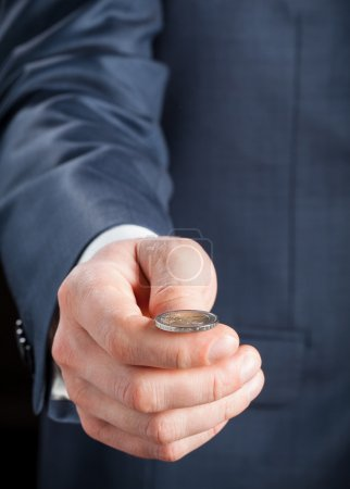 Photo for Businessman tossing a coin - closeup shot - Royalty Free Image