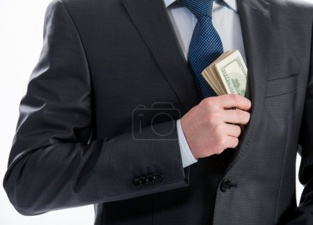 Businessman putting money in his pocket
