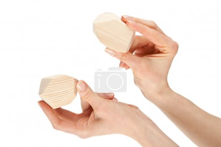 Hands showing two wooden blocks