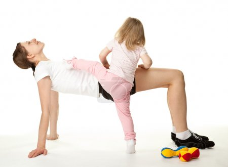 Happy young woman and her daughter doing sport exercises