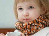 Das Babymädchen mit einer Tasse Tee