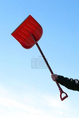 Hand holding red shovel