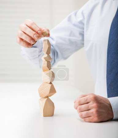Businessman making tower of wooden blocks