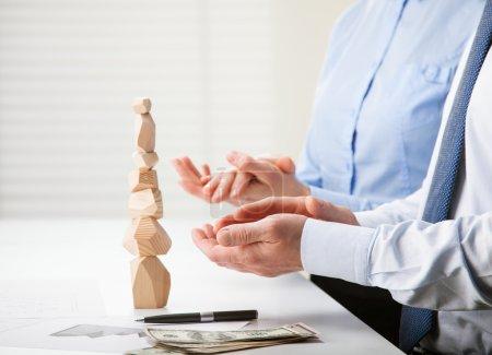 Photo pour Des hommes d'affaires applaudissant près de la tour en bois construite (jeu japonais tumi-ishi), illustrant le concept de réussite commerciale, de coopération, de réussite et de maîtrise de soi - image libre de droit