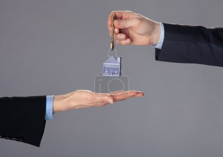 Businessman's hand passing a key to woman's hand