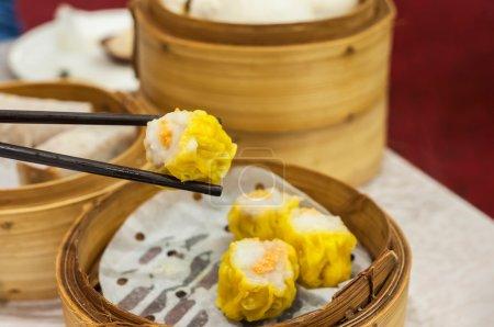 Photo pour Shumai est l'un des plats les plus populaires de tous les dim sum, généralement composé d'une boulette de porc et de crevettes garnie de poisson ou d'oeufs de crabe, tels que ceux vus ici . - image libre de droit