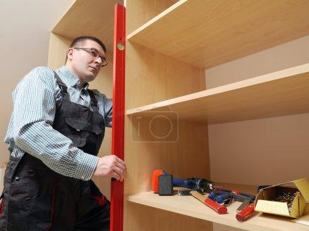 Photo pour Menuisier à l'aide de niveau à bulle pour le nivellement assemblé meubles armoire - image libre de droit